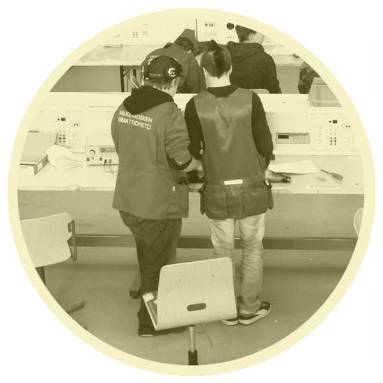 Kaksi opiskelijaa työskentelee seisten työpöydän äärellä. Takanaan heillä on odottamassa työtuolit.