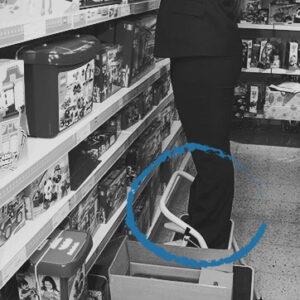 En person använder en plattform när han plockar upp saker från översta hyllan.