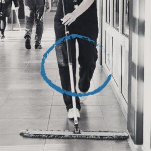 Personen håller i en rengöringsmopp och skjuter den framför sig medan hen går.