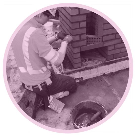 Studenten utför murarbeten med sakenliga verktyg och skyddsutrustning. Klädd i arbetskläder, arbetsskor, hjälm, skyddsglasögon.