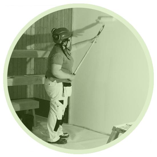 Studenten målar en vägg med en färgroller och skaft. Klädd i skyddsutrustning såsom overall, skyddsglasögon, hjälm, på vilken det sitter hörselskydd.