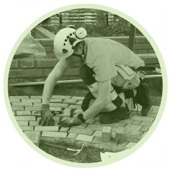 A student lays bricks on the ground for flooring. Wearing protective equipment (workwear, gloves, goggles and helmet (also wearing hearing protection)