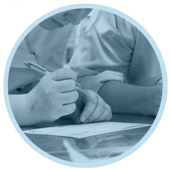 Studenten koncentrerar sig på att skriva på ett papper med en penna i handen.
