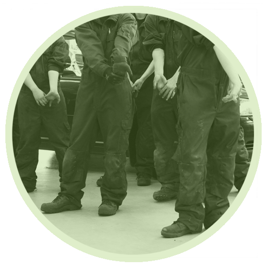 Students in work overalls warming up and stretching their wrists by bending.