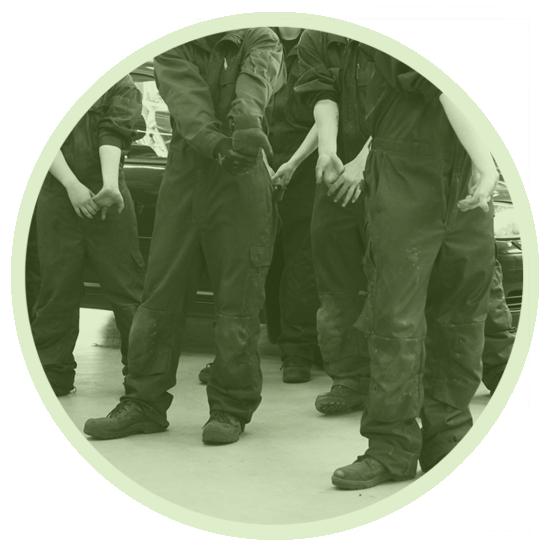 Studenter i arbetsoveraller värmer upp och stretchar handlederna genom att böja dem.