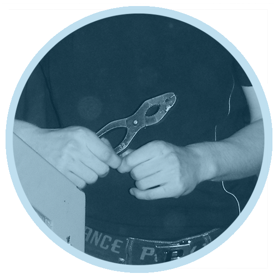 A person holds a tool thoughtfully in his hands.
